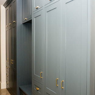 Design ideas for a medium sized traditional gender neutral walk-in wardrobe in Other with shaker cabinets, blue cabinets, travertine flooring and brown floors.