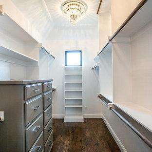 Modelo de armario vestidor unisex, de estilo de casa de campo, grande, con armarios con paneles con relieve, puertas de armario azules, suelo de madera oscura y suelo marrón