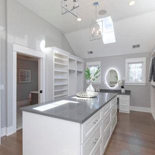 Ejemplo de armario vestidor unisex, de estilo de casa de campo, grande, con armarios abiertos, puertas de armario blancas, suelo de madera clara y suelo marrón