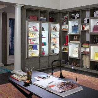 Immagine di un ampio spazio per vestirsi per donna moderno con ante di vetro, parquet scuro e pavimento grigio