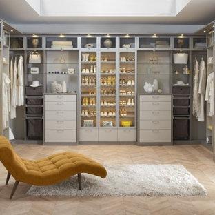 Inspiration för ett funkis walk-in-closet för kvinnor, med grå skåp, släta luckor och ljust trägolv
