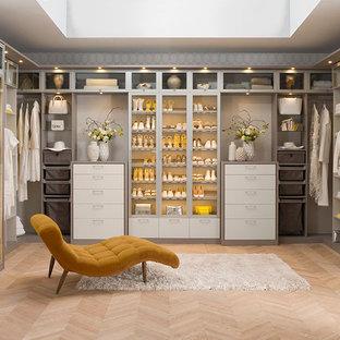 Idées déco pour un grand dressing moderne pour une femme avec un sol en bois clair, un placard à porte plane et des portes de placard beiges.