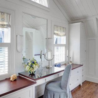 Immagine di una cabina armadio per donna stile marinaro di medie dimensioni con ante bianche, pavimento in legno massello medio e ante con riquadro incassato