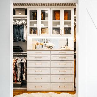 Modelo de armario vestidor unisex, tradicional renovado, de tamaño medio, con armarios estilo shaker, puertas de armario blancas, suelo de madera en tonos medios y suelo marrón