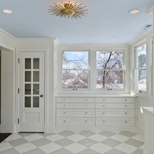 На фото: гардеробная комната в классическом стиле с белыми фасадами и полом из керамической плитки с