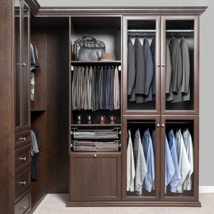 This is an example of a large contemporary men's walk-in wardrobe in Other with brown cabinets and recessed-panel cabinets.