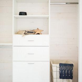 Foto de armario unisex, marinero, pequeño, con armarios con paneles lisos, puertas de armario blancas y suelo de madera oscura