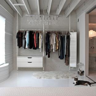 Diseño de armario y vestidor actual con armarios con paneles lisos, puertas de armario blancas y suelo de baldosas de cerámica