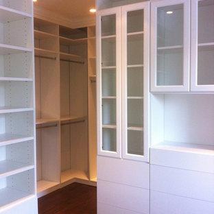 Modelo de armario vestidor unisex, clásico, grande, con armarios con paneles lisos, puertas de armario blancas y suelo de madera en tonos medios