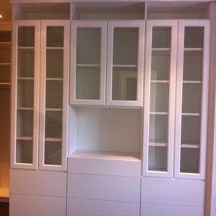Foto de armario vestidor unisex, tradicional, grande, con armarios tipo vitrina, puertas de armario blancas y suelo de madera en tonos medios