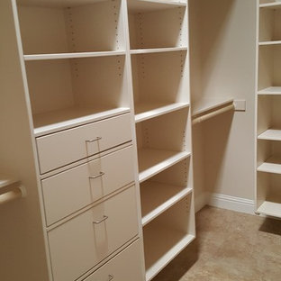 Large contemporary gender neutral walk-in wardrobe in Sacramento with flat-panel cabinets, white cabinets and travertine flooring.