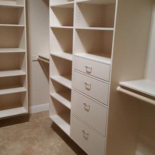 Imagen de armario vestidor unisex, actual, grande, con armarios con paneles lisos, puertas de armario blancas y suelo de travertino