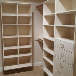 This is an example of a large contemporary gender neutral walk-in wardrobe in Sacramento with flat-panel cabinets, white cabinets and travertine flooring.