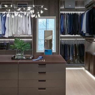 Modelo de vestidor de hombre, actual, extra grande, con armarios con paneles lisos, puertas de armario marrones, suelo de madera clara y suelo beige