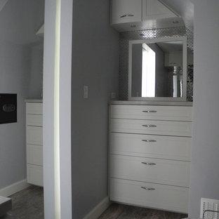 Immagine di una piccola cabina armadio unisex design con ante in stile shaker, ante bianche e pavimento in travertino