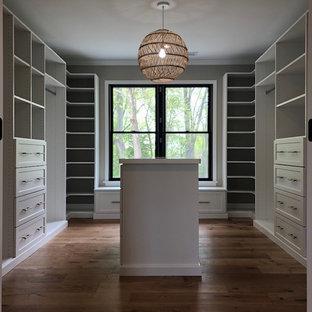 Ejemplo de armario vestidor de estilo de casa de campo, de tamaño medio, con armarios estilo shaker, puertas de armario blancas y suelo de madera en tonos medios