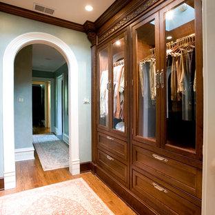 Foto de armario clásico con armarios tipo vitrina y puertas de armario de madera en tonos medios