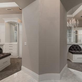 Immagine di un grande spazio per vestirsi per donna mediterraneo con ante bianche, moquette e pavimento grigio