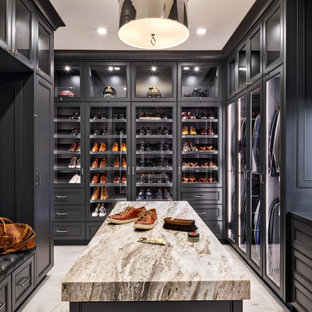Inspiration for a mediterranean men's walk-in wardrobe in Phoenix with glass-front cabinets and black cabinets.