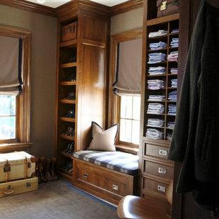Diseño de vestidor de hombre, clásico, con armarios con paneles empotrados, puertas de armario de madera oscura, moqueta y suelo azul