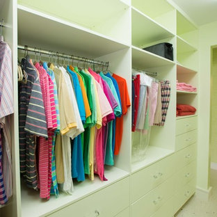 World-inspired gender neutral wardrobe in Miami with flat-panel cabinets, green cabinets and travertine flooring.