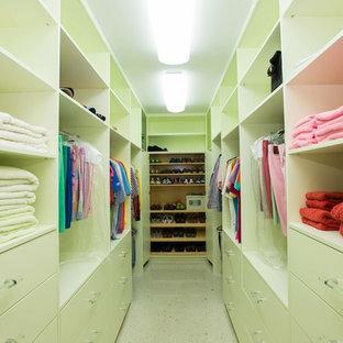 Diseño de armario y vestidor unisex, tropical, con armarios con paneles lisos, puertas de armario verdes y suelo de travertino