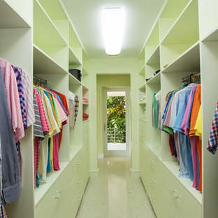 Photo of a world-inspired gender neutral wardrobe in Miami with flat-panel cabinets, green cabinets and travertine flooring.