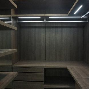 Modelo de armario vestidor de hombre, minimalista, pequeño, con puertas de armario de madera en tonos medios y suelo de baldosas de porcelana