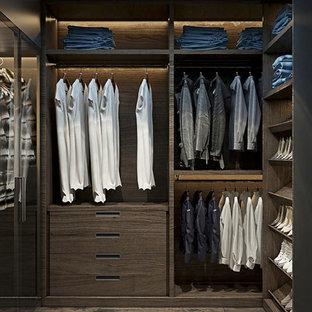 Ejemplo de armario vestidor unisex, minimalista, grande, con armarios con paneles lisos, puertas de armario de madera en tonos medios, suelo de madera oscura y suelo marrón