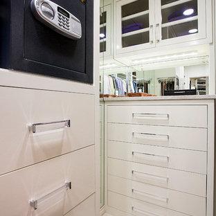 Diseño de armario vestidor de hombre, clásico, grande, con armarios con paneles lisos, puertas de armario blancas, moqueta y suelo beige