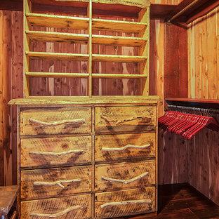 Aménagement d'un dressing montagne de taille moyenne et neutre avec un placard à porte plane, des portes de placard en bois vieilli et un sol en bois foncé.