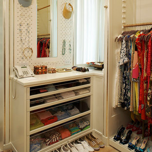 Example of a transitional reach-in closet design in New York with open cabinets and white cabinets