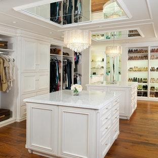 Imagen de vestidor de mujer, clásico, extra grande, con armarios con rebordes decorativos, puertas de armario blancas, suelo marrón y suelo de madera oscura