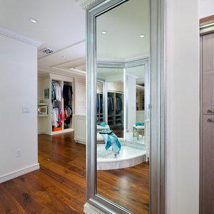 Ejemplo de vestidor de mujer, tradicional, extra grande, con armarios con rebordes decorativos, suelo de madera clara y puertas de armario blancas
