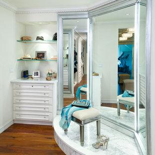 Ispirazione per un ampio spazio per vestirsi per donna classico con ante bianche, pavimento in legno massello medio e pavimento marrone