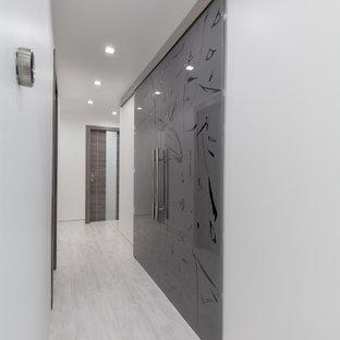 Foto di un armadio o armadio a muro unisex minimalista di medie dimensioni con ante di vetro, ante grigie, pavimento in laminato e pavimento grigio