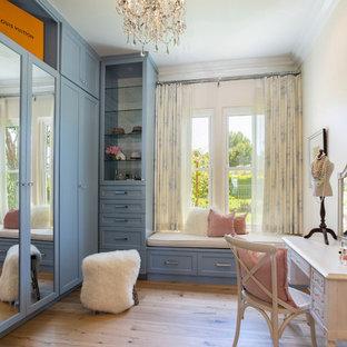 Diseño de vestidor de mujer, marinero, de tamaño medio, con armarios estilo shaker, puertas de armario azules, suelo de madera en tonos medios y suelo marrón