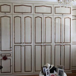 Modelo de vestidor unisex, clásico, de tamaño medio, con armarios con paneles con relieve, puertas de armario con efecto envejecido y suelo de madera clara