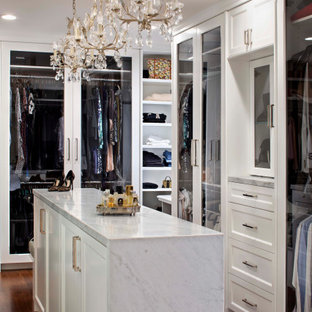 サンフランシスコの中くらいの男女兼用地中海スタイルのおしゃれなフィッティングルーム (白いキャビネット、無垢フローリング、茶色い床、ガラス扉のキャビネット、三角天井) の写真