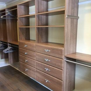 Imagen de armario vestidor unisex, bohemio, grande, con puertas de armario de madera oscura y suelo de madera en tonos medios