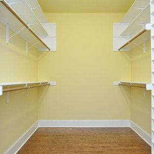 Diseño de armario vestidor unisex, grande, con suelo de madera en tonos medios