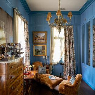 Aménagement d'un dressing et rangement classique avec un placard avec porte à panneau encastré, des portes de placard bleues, un sol en bois foncé et un sol marron.