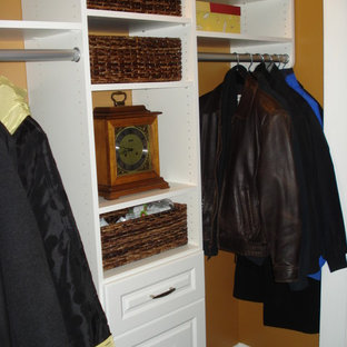 Example of a mid-sized classic gender-neutral slate floor reach-in closet design in Boston with raised-panel cabinets and white cabinets