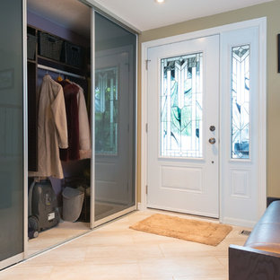 Medium sized contemporary gender neutral wardrobe in Ottawa with flat-panel cabinets and travertine flooring.