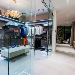 Modelo de vestidor moderno, extra grande, con armarios con paneles lisos, puertas de armario de madera en tonos medios, suelo de mármol y suelo gris