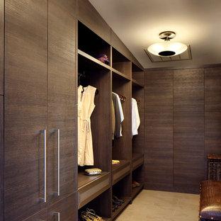 Idée de décoration pour un grand dressing room design neutre avec un placard à porte plane, des portes de placard en bois sombre et un sol en travertin.