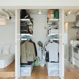 Foto de armario vestidor de hombre, industrial, pequeño, con puertas de armario blancas y suelo de madera clara