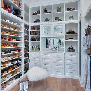 Ejemplo de vestidor de mujer, mediterráneo, con armarios abiertos, puertas de armario blancas y suelo de madera en tonos medios