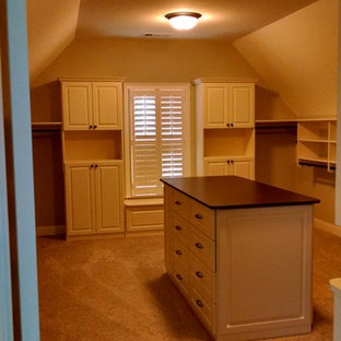 Photo of a mid-sized traditional gender-neutral walk-in wardrobe in Atlanta with raised-panel cabinets, white cabinets and carpet.