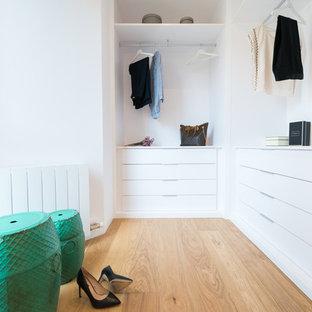 Modelo de armario vestidor de mujer, escandinavo, de tamaño medio, con puertas de armario blancas, armarios con paneles lisos y suelo de madera clara